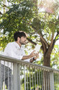 Young man leaning on railing in the city holding tablet - GIOF04842