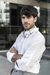 Portrait of confident young man wearing headphones in the city - GIOF04851