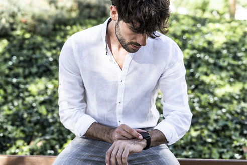 Young man sitting outdoors using smartwatch - GIOF04860