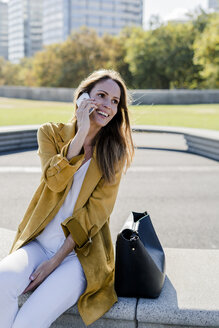 Happy woman with bag and cell phone sitting on a bench in the city - GIOF04875
