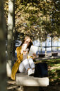 Woman sitting on a bench in a park using tablet - GIOF04890
