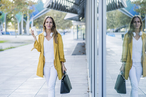 Woman with handbag and takeaway coffee walking along building - GIOF04896