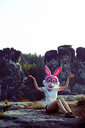 A person in a bunny mask embracing nature by the rocks - INGF08266