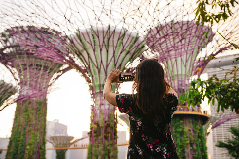 Singapore, Gardens by the Bay, woman taking cell phone picture in Supertree Grove at sunset - GEM02638