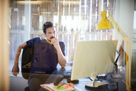 Creative businessman looking at computer monitor while sitting in office - MASF10153