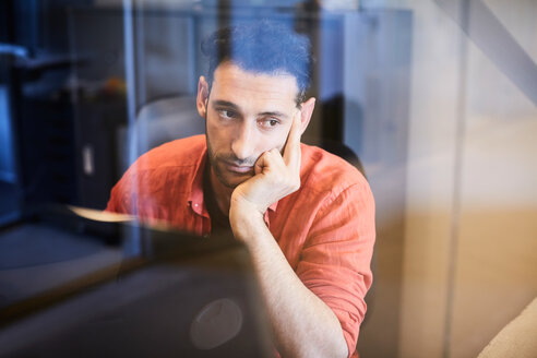 Thoughtful businessman looking through glass while sitting at computer desk in office - MASF10162