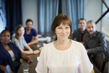 Portrait of confident mature businesswoman standing while colleagues in background at office - MASF10177