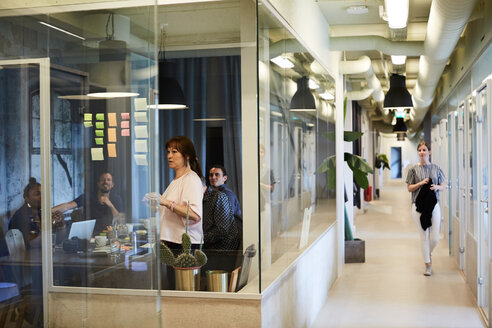 Business people brainstorming ideas in board room while female colleague walking in corridor - MASF10189