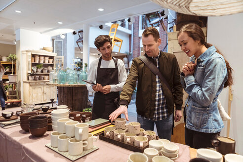 Salesman assisting couple in buying crockery at boutique - MASF10216