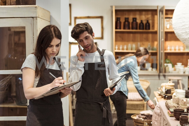 Male entrepreneur using phone while looking at female colleague writing on clipboard in boutique - MASF10219 - Kentaroo Tryman/Westend61