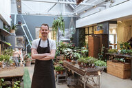 Portrait of smiling owner standing with arms crossed against potted plants at store - MASF10237