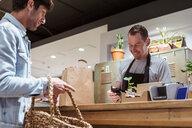 Customer paying cashier at checkout counter - MASF10249
