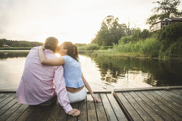 Rear view of boyfriend kissing girlfriend sitting with arms around on jetty over lake during sunset - MASF10264