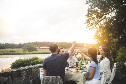 Male and female friends toasting drinks at dining table against sky during sunset - MASF10267