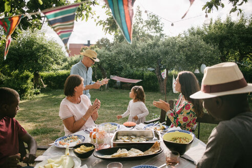 Family applauding at senior man and girl dancing during garden party - MASF10270