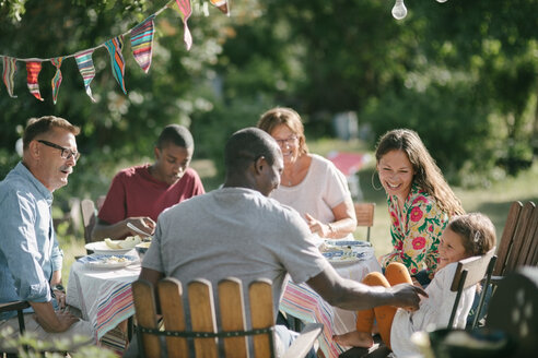 Happy multi-generation family having lunch together in backyard during garden party - MASF10276
