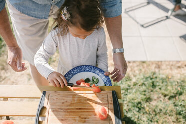 Girl putting tomato slices in plate with knife while standing by grandfather at table during garden party - MASF10285