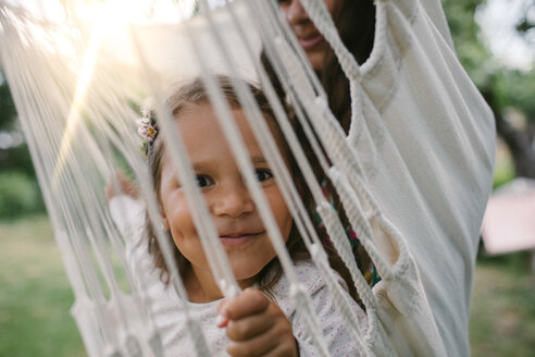 Portrait of smiling girl seen through ropes while swinging with mother on hammock in backyard - MASF10291