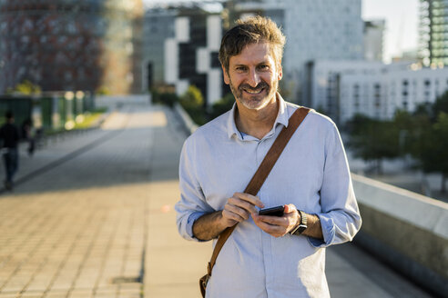 Portrait of smiling mature man with cell phone in the city - GIOF04908