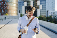 Mature man with takeaway coffee and headphones using cell phone in the city - GIOF04911