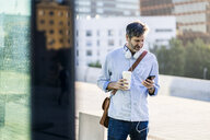 Mature man with takeaway coffee and headphones using cell phone in the city - GIOF04914