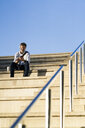 Mature man sitting on steps with headphones and cell phone - GIOF04917