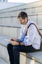 Mature man sitting on steps using tablet - GIOF04920