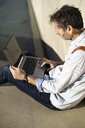 Mature man sitting on steps using laptop - GIOF04932