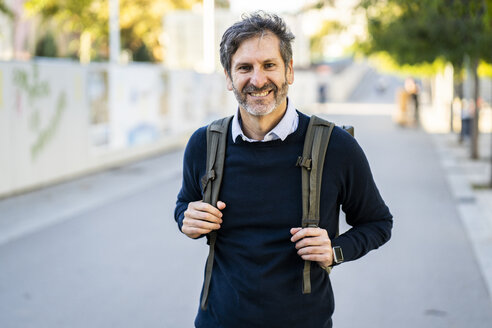Portrait of smiling mature man wearing a backpack in the city - GIOF04935