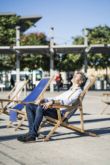Mature man relaxing in deckchair on a square in the city - GIOF04947