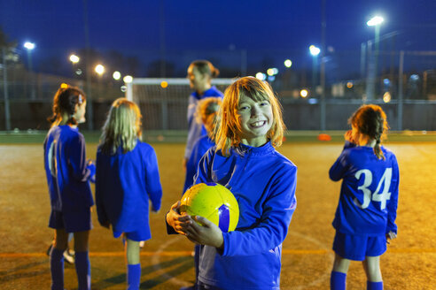 Portrait smiling, enthusiastic girl enjoying soccer practice on field at night - HOXF04191