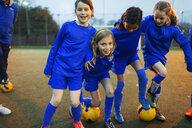 Portrait happy girls soccer team on field - HOXF04209