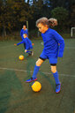 Girl soccer player practicing on field - HOXF04215