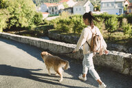 Woman walking with her golden retriever dog on a road - RAEF02227