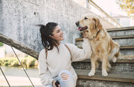 Smiling young woman stroking her Golden retriever dog on stairs outdoors - RAEF02233