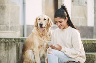 Young woman with her Golden retriever dog on stairs outdoors using cell phone - RAEF02239