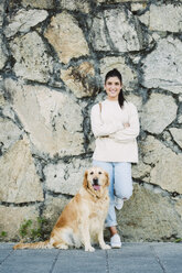 Portrait of a smiling young woman with her Golden retriever dog at a stone wall - RAEF02242