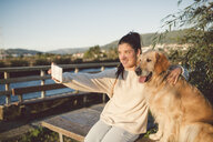 Smiling young woman taking a selfie with her dog at the waterfront - RAEF02248