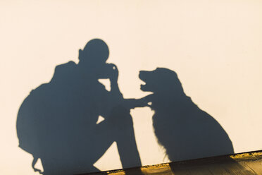 Shadow of a photographer and dog on a white wall - RAEF02251