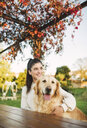 Smiling young woman with her Golden retriever dog resting in a park - RAEF02254