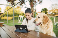 Smiling young woman using a tablet in a park with her dog - RAEF02257