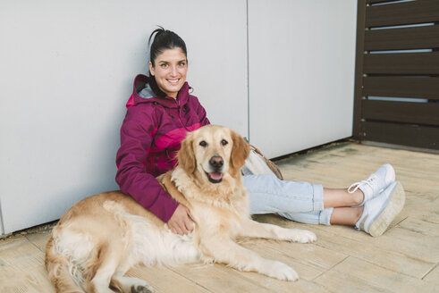 Portrait of a smiling young woman with her Golden retriever dog sitting at a wall - RAEF02263