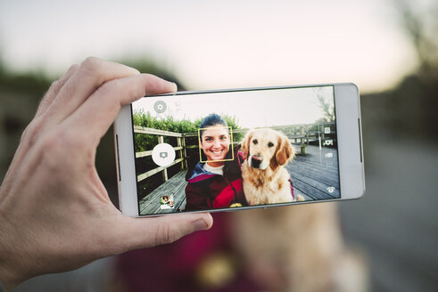 Cell phone picture of a happy young woman with her Golden retriever dog outdoors - RAEF02266