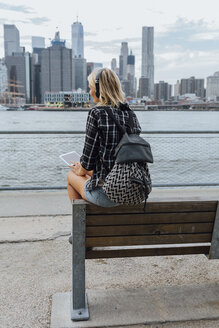 USA, New York City, Brooklyn, young woman sitting at the waterfront with backpack, headphones and tablet - BOYF01122