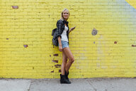 Portrait of young woman with cell phone at yellow brick wall - BOYF01131