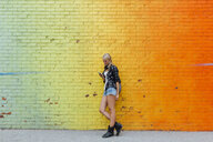 Young woman checking cell phone at colorful brick wall - BOYF01134
