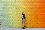 Young woman checking cell phone at colorful brick wall - BOYF01134