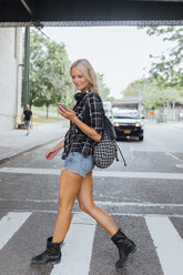USA, New York City, Brooklyn, smiling young woman with cell phone crossing the street - BOYF01137