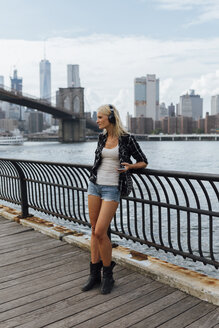 USA, New York City, Brooklyn, young woman standing at the waterfront with headphones and cell phone - BOYF01146