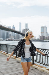 USA, New York City, Brooklyn, happy young woman with headphones and cell phone dancing at the waterfront - BOYF01149